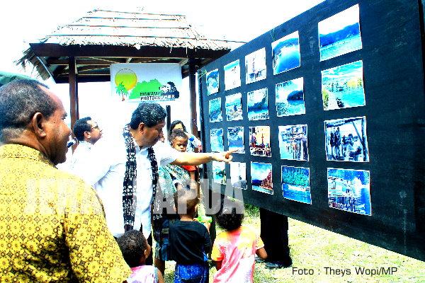Bupati Yapen dan Anak-anak Kampung Sarawandori sedang melihat foto-foto (foto : Theys Wopi/MP)